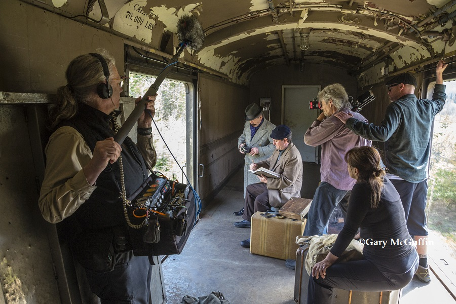 Phyllis Ellis directing reenactment scene in ACR boxcar from Painted Land.