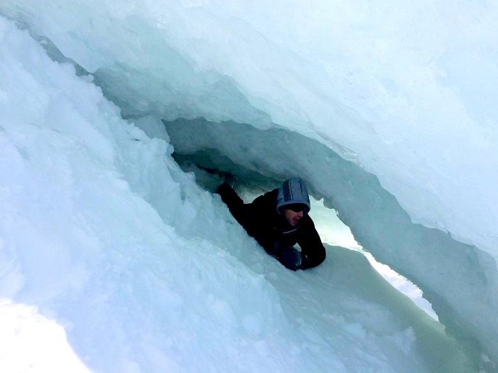 Squeezing through an Ice Cave on Old Woman Bay. Photo credit: Meaghan Kent