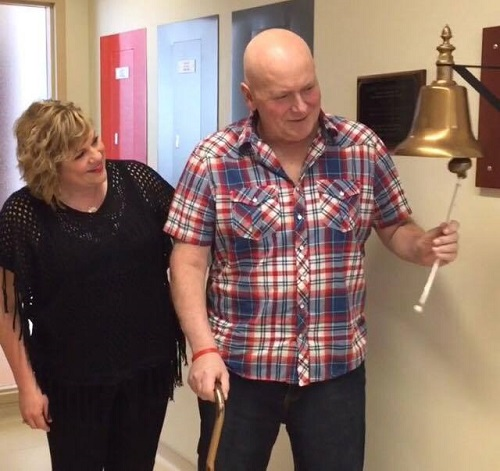 Happy day! Brian rings the bell with Faith and loved ones by his side.